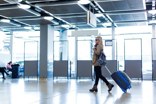 Турист путешественника женщины идя с багажом на вокзале. концепция активного и путешествующего образа жизни