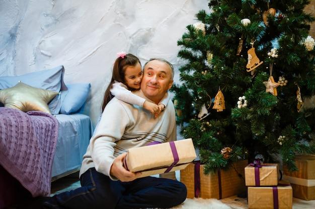 祖父と孫娘のクリスマスツリーの近く