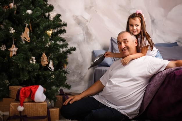 かわいい歯のない少女と彼女の祖父が自宅のクリスマスツリーを飾る