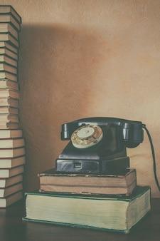 古い黒い電話と書籍のスタック
