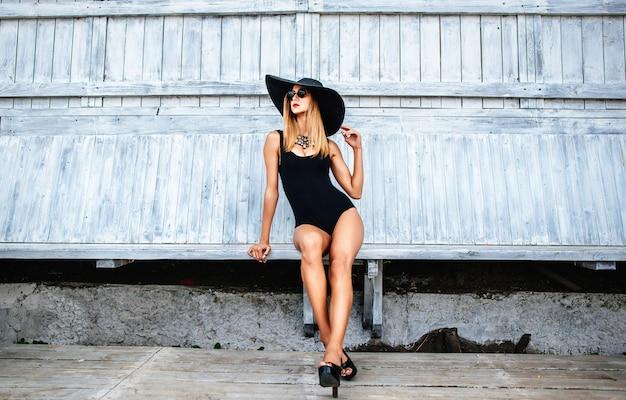 黒の水着で屋外でリラックスできるかなり若い女の子