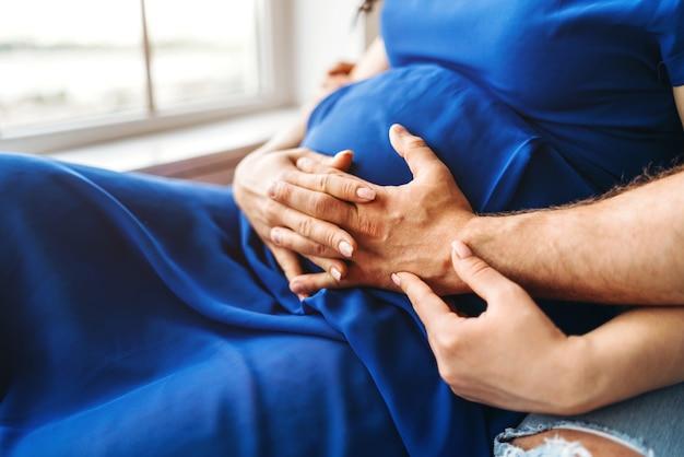 Симпатичные беременная женщина обнимаются с мужем