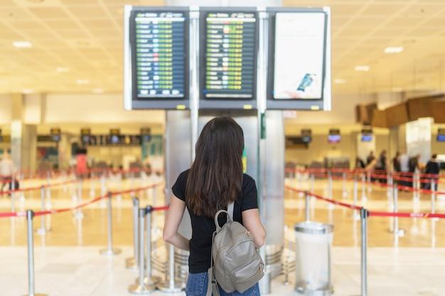 Брюнетка длинные волосы девушка ждет вылета в аэропорту.