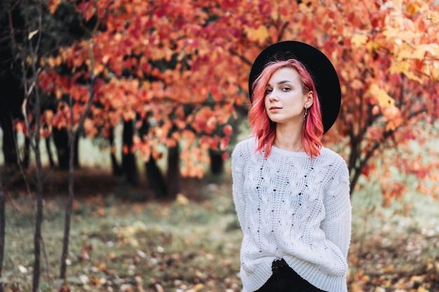 秋の時間、公園を歩いて赤い髪と帽子でかわいい女の子。