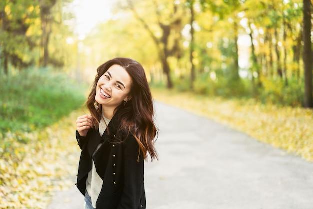 公園でリラックスしたかなり長い髪のブルネットの少女