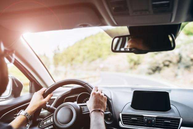 男は内側からの眺めと車を運転します。
