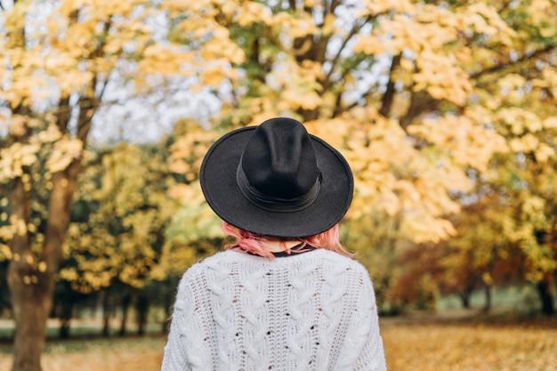 秋の時間、公園でリラックスした赤い髪と帽子の美少女。