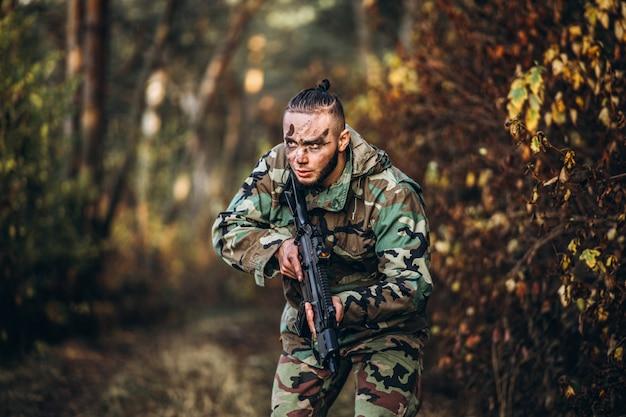 Камуфляжный солдат с ружьем и раскрашенным лицом играет в страйкбол на улице в лесу
