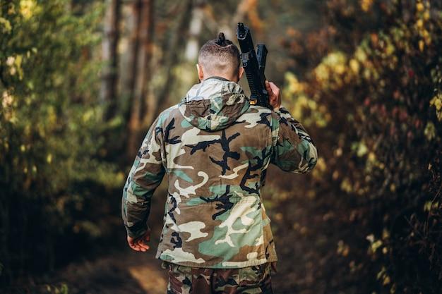 Солдат в камуфляжной форме с винтовкой на плече гуляет в лесу.