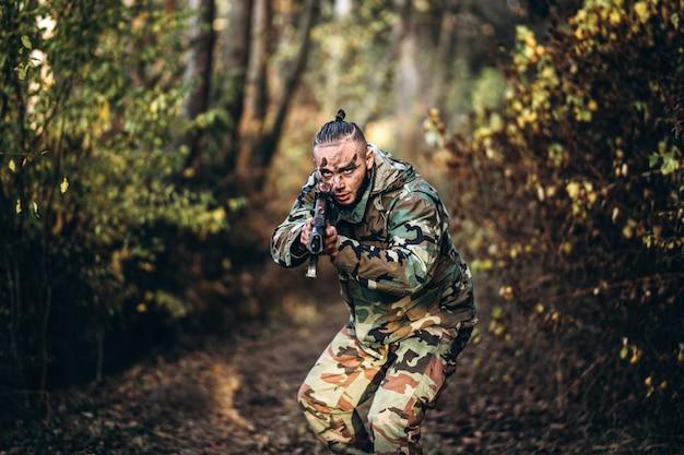 ライフルとエアソフトフォレストで野外で遊ぶ塗装面を持つ兵士をカモフラージュします。