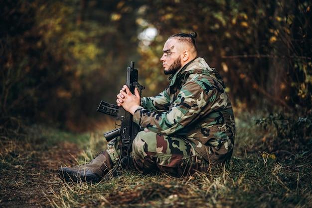 ライフルと草の中に座って塗装面を持つ兵士をカモフラージュします。