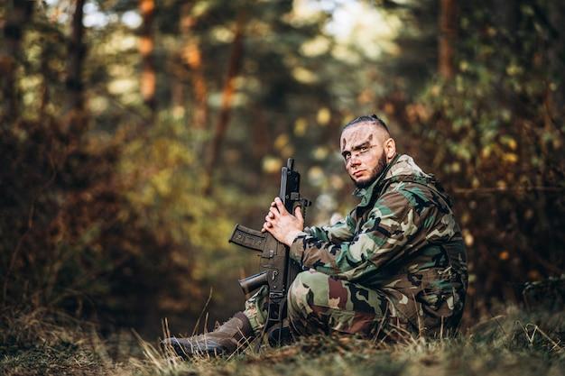 Камуфляжный солдат с винтовкой и раскрашенным лицом, сидящий в траве.