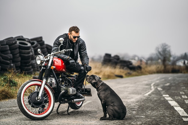 Бородатый мужчина в солнцезащитные очки и кожаную куртку, улыбаясь сидя на красный мотоцикл на дороге со своей собакой.