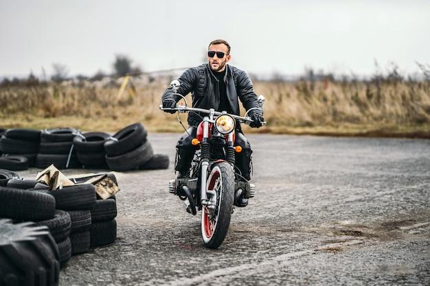 サングラスと赤いバイクの上に座って、道路を見ている革のジャケットのひげを生やした男。