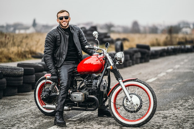 Красный мотоцикл с наездником. человек в черной кожаной куртке и брюках стоит боком посреди дороги.
