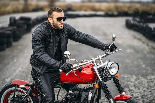 ライダーと赤いバイク。黒い革のジャケットとズボンを着た男が道路の真ん中に横に立っています。タイヤは背景に置かれます