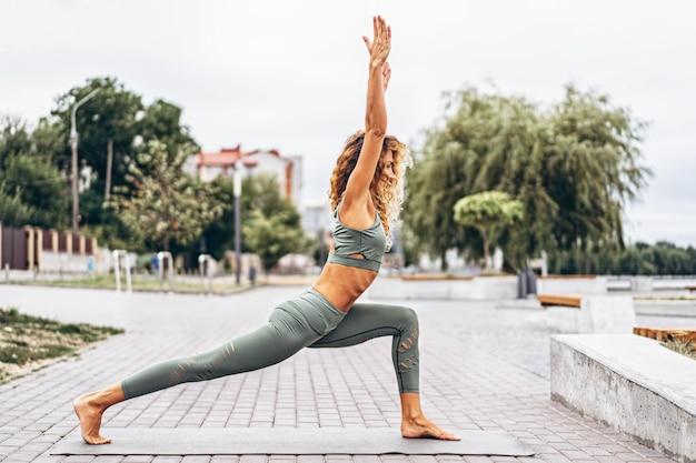 路上でストレッチ体操を行う灰色のトラックスーツに長い髪を持つスポーティな若い女性