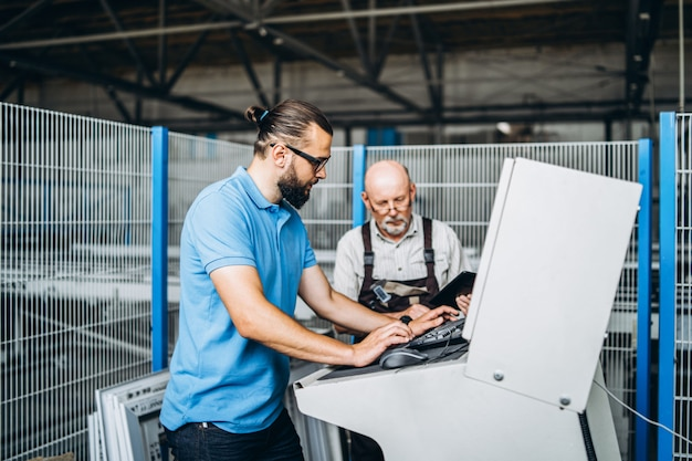 Двое мужчин, старший инженер и менеджер проекта, проверяют производственные данные возле машин на заводе