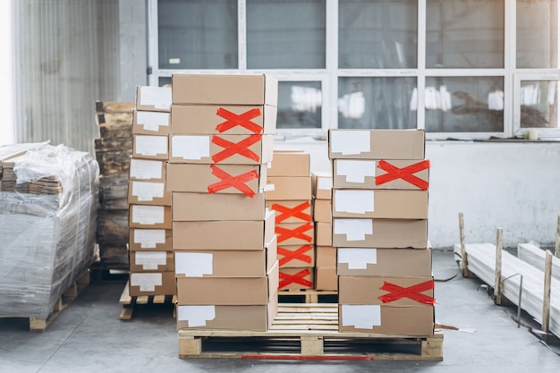 Стопки картонных коробок с продукцией в заводской упаковочной мастерской. некоторые из них помечены красной лентой