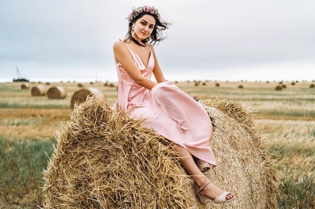 干し草のベールの上に座ってピンクのサテンのドレスの若いブルネット。女性は頭に花輪を持ち、野生の花の花束を手に持っています