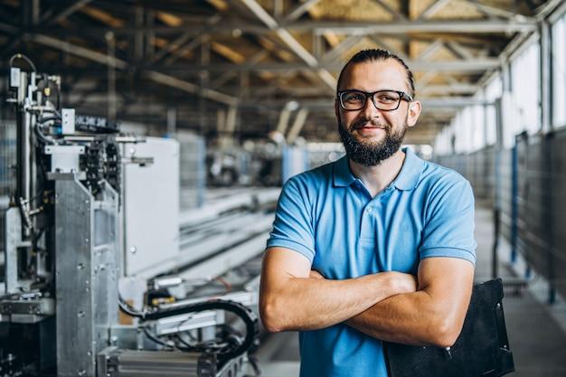 Усмехаясь работник в стеклах стоя около промышленного оборудования и смотря камеру. мужчина держит папку в руках