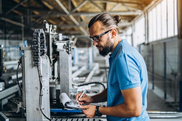 Рабочий в очках стоит возле промышленного оборудования и проверяет производственные данные. мужчина держит папку в руках