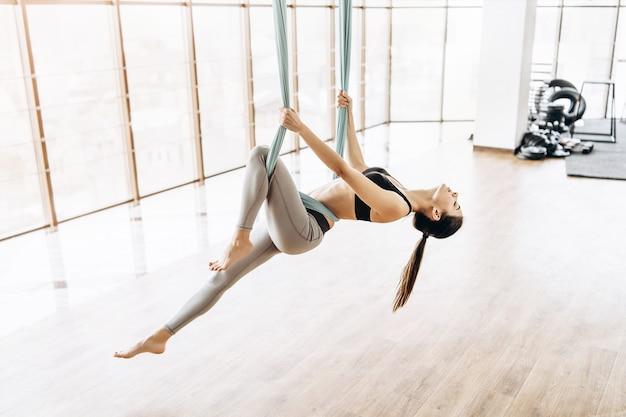 若いかなりスリムボディフィットネス女の子がジムでハエのヨガの練習します。