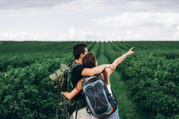 Вид сзади молодая пара с рюкзаками на плантации смородины. женщина с длинными волосами указывает рукой на горизонт