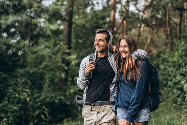 Молодая пара с рюкзаками на спине улыбаются и гуляют в лесу, наслаждаются прогулкой