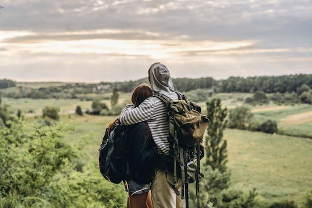 Вид сзади молодая пара с рюкзаками. мужчина и женщина обнимаются и смотрят пейзаж сельской местности