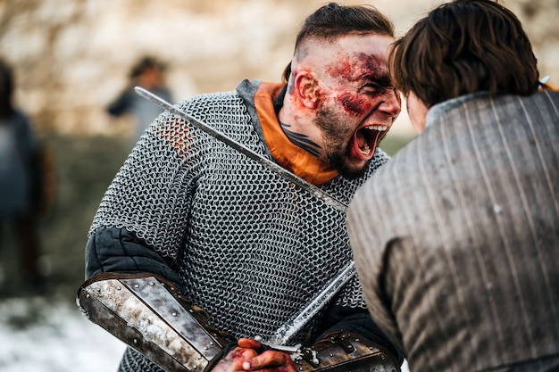 Два воина в доспехах с оружием сражаются на мечах. крупный план эмоций на лице воина, измазанного кровью