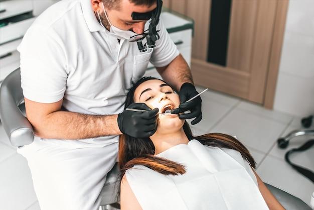 歯科医が椅子にメスの患者と歯科医院で働く