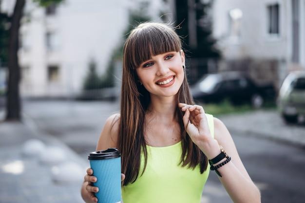 Милая брюнетка в зеленом платье с чашечкой кофе гуляет на улице