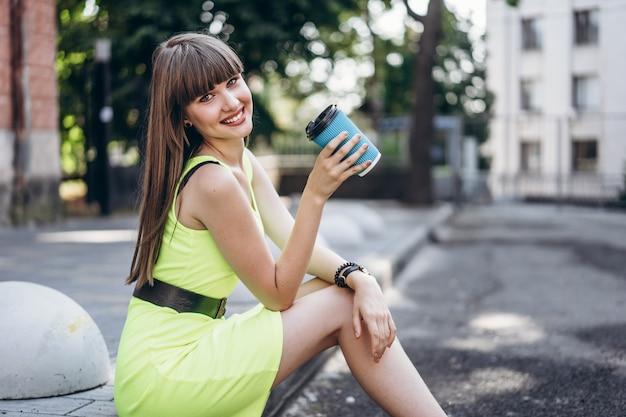 Милая брюнетка девушка в зеленом платье с чашкой кофе, сидя на улице