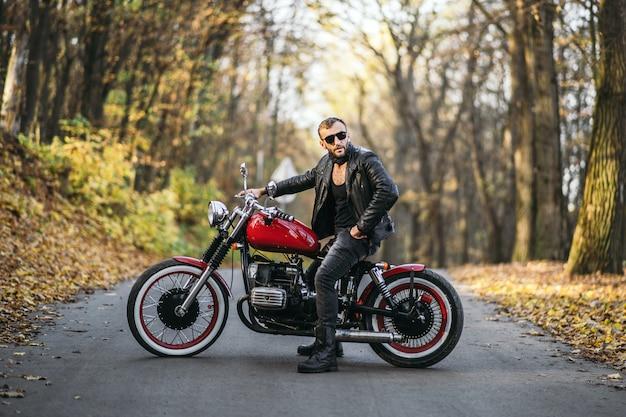 Бородатый брутальный мужчина в темных очках и кожаной куртке сидит на мотоцикле на дороге в лесу