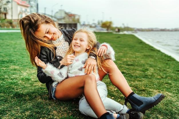 彼女の小さな娘を持つ母は公園で楽しんでいます