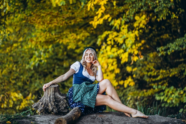 Босая счастливая симпатичная белокурая девушка в дирндле, традиционном пивном фестивальном платье, сидя на открытом воздухе с размытыми разноцветными деревьями