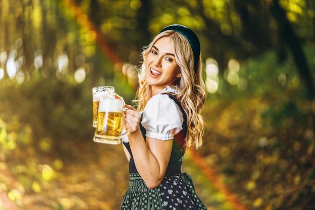 Довольно счастливая блондинка в дирндль, традиционном фестивальном платье, держит две кружки пива на улице в лесу