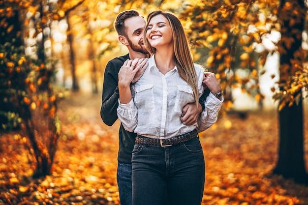 晴れた日に秋の公園を歩いて恋に若いカップル