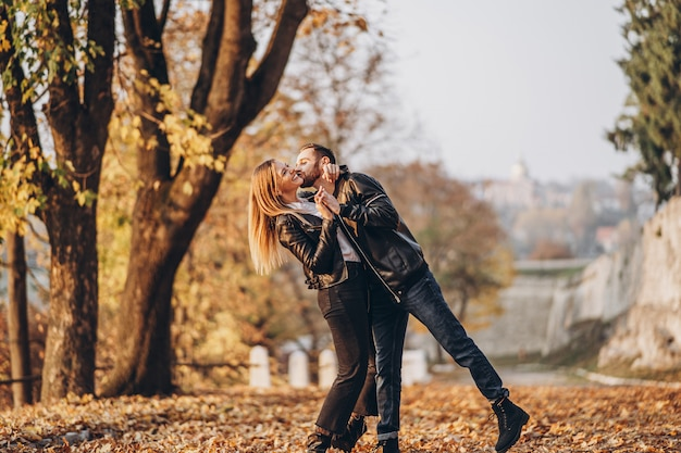 秋の公園で屋外を歩く幸せな愛情のあるカップルの完全な長さの肖像画。