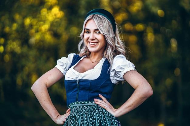 Портрет счастливой довольно белокурой девушки в дирндле, традиционном пивном фестивальном платье, стоя на улице с размытыми красочными деревьями позади