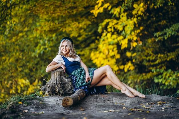 Босая счастливая симпатичная белокурая девушка в дирндле, традиционном пивном фестивальном платье, сидя на открытом воздухе с размытыми разноцветными деревьями позади