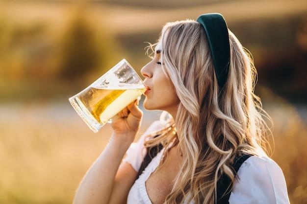 Довольно счастливая блондинка в дирндль, традиционное фестивальное платье, пьет пиво на свежем воздухе в поле