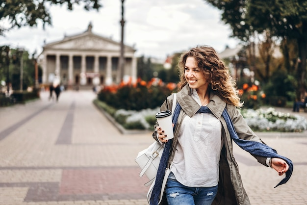 Счастливая девушка с вьющимися волосами наслаждаться напитком на открытом воздухе