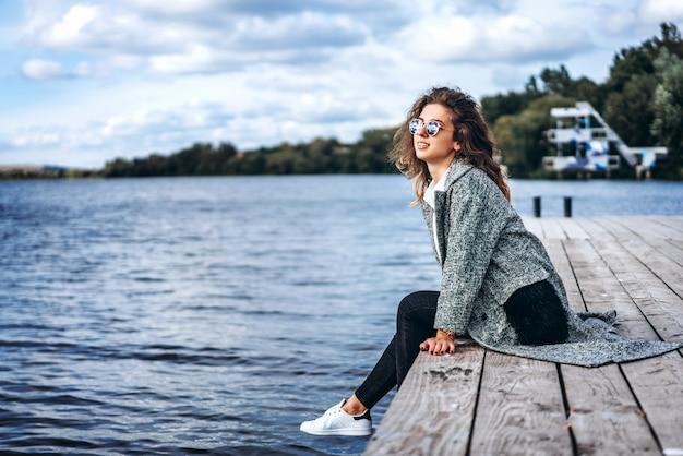 湖の近くリラックスした巻き毛を持つかわいい女の子