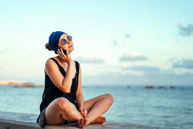かなりブルネットの観光客の女の子は屋外の電話で話します