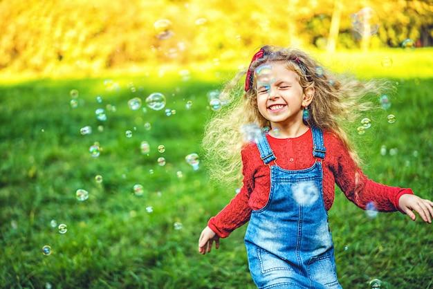 かわいい女の子が公園でシャボン玉を吹いています。