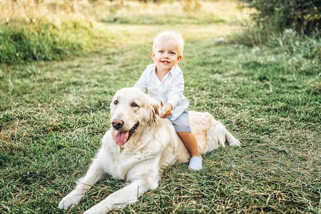 Симпатичный маленький мальчик веселиться с собакой