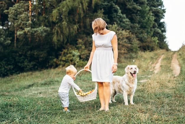 息子と屋外のピクニックに犬を持つ母