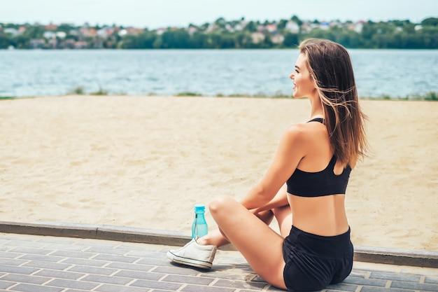 トレーニング後屋外でリラックスできるスポーティなかわいい女の子